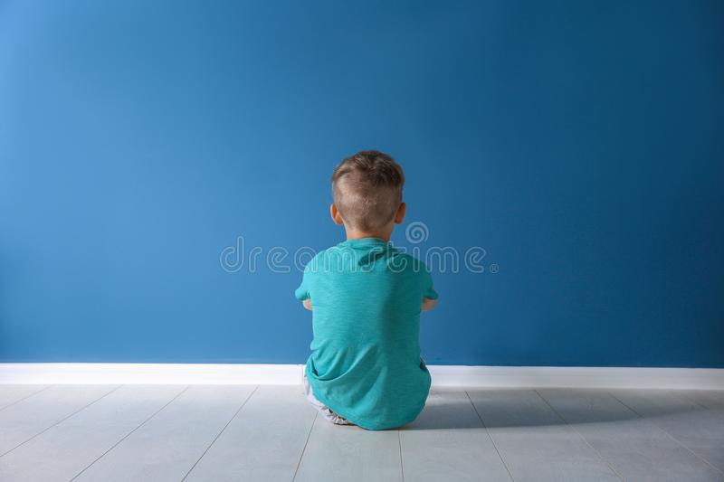 Little boy sitting on floor near color wall in empty room royalty free stock photos