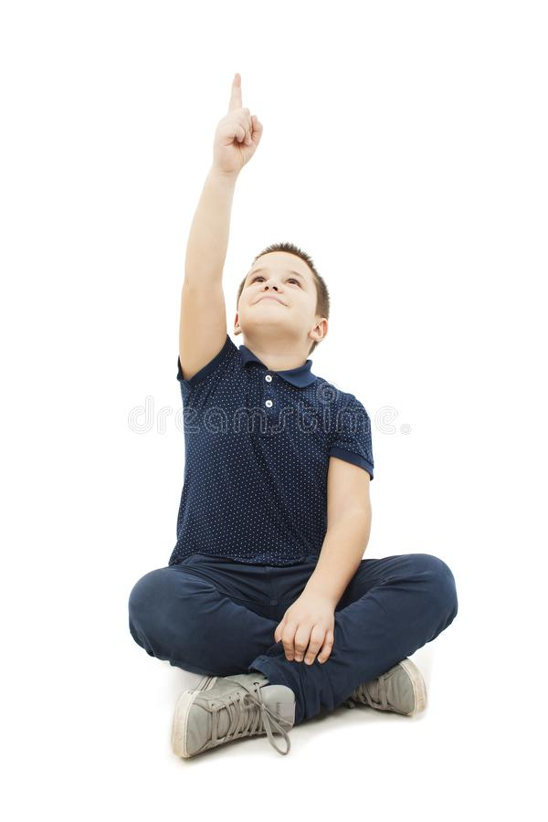 Little boy sitting on floor pointing empty copy space royalty free stock photography