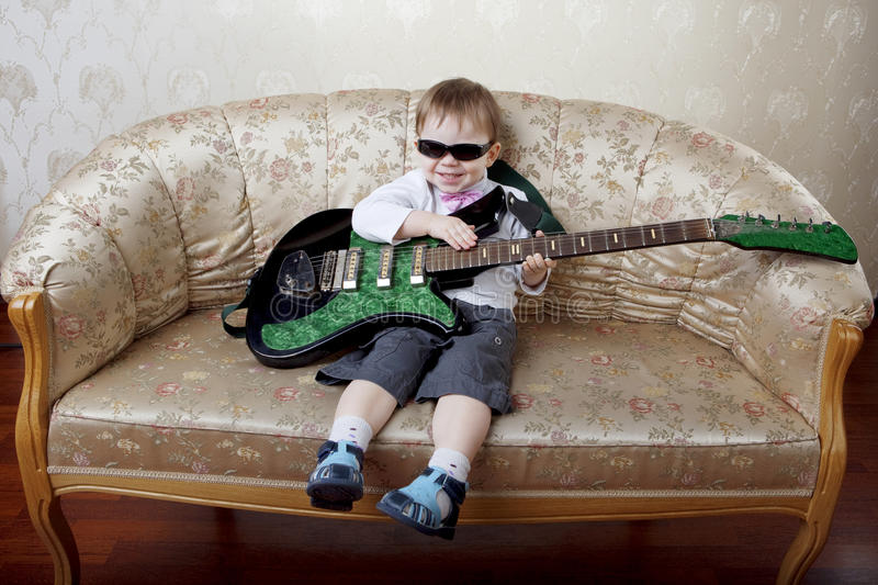 Little boy sitting on the glamorous couch stock image