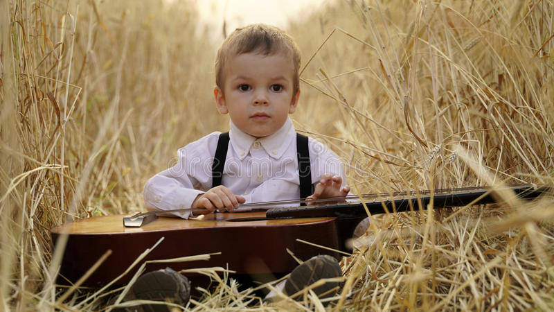 Little boy sitting in a golden wheat field and playing the guitar. royalty free stock images