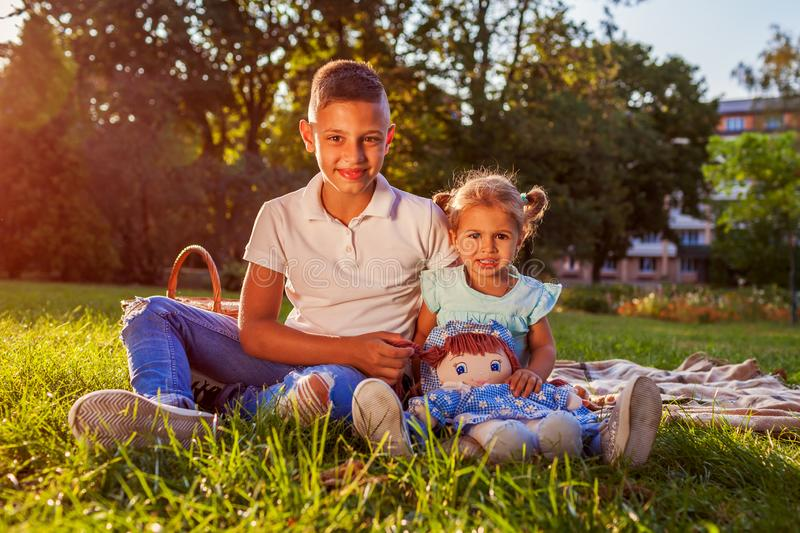 Little boy sitting on grass with his toddler sister in park. Happy family having picnic. Family values royalty free stock photo