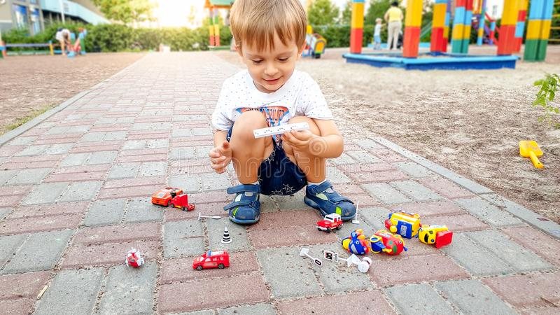Little toddler boy sitting on the ground at park and playing with toy cars. Little boy sitting on the ground at park and playing with toy cars stock image