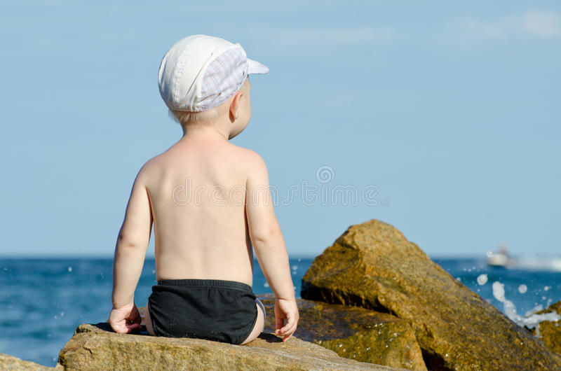Little boy sitting with his back to a rock on the seashore in swimming trunks, blue sky, space for text.  royalty free stock images