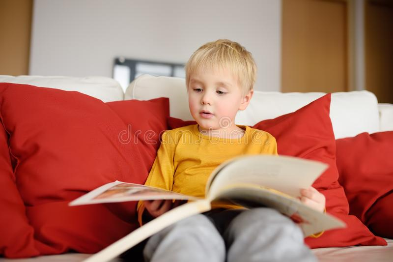 Little boy is sitting at home on the couch and reading a book. Learning to read royalty free stock photography