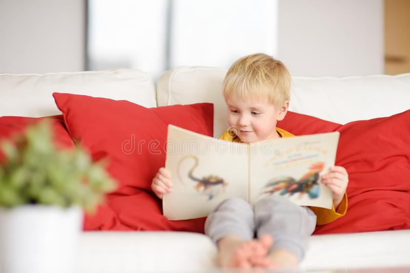 Little boy is sitting at home on the couch and reading a book. Learning to read stock photography