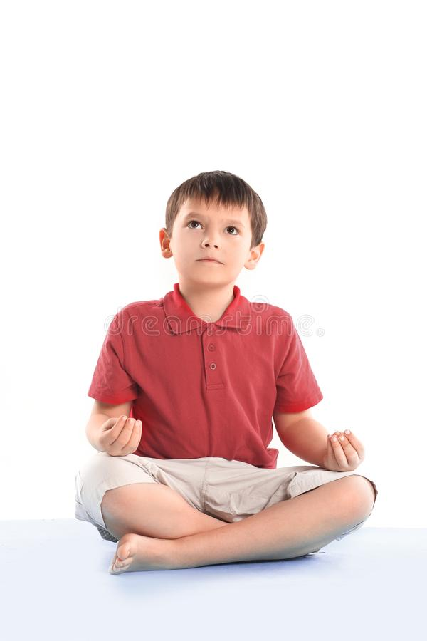Little boy is sitting in the Lotus position.isolated on white stock image