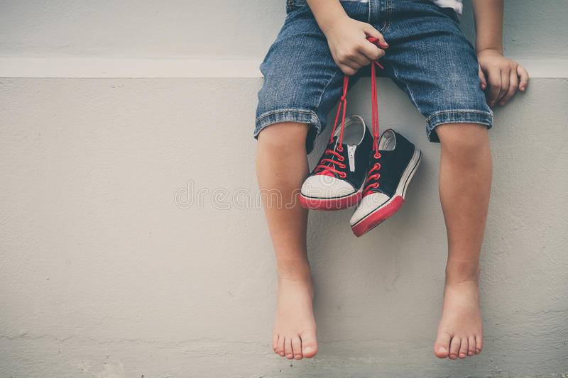 Little boy sitting near the house and keeping the youth sneaker. S in his hands of at the day time stock photos