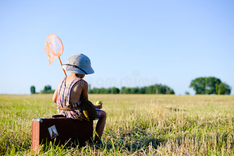 Little boy sitting on old brown suitcase eating royalty free stock image