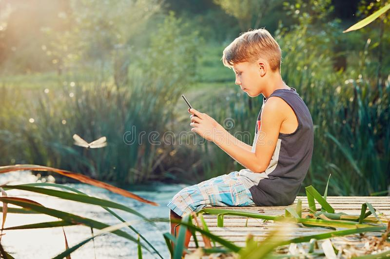 Little boy sitting on the pier of the lake royalty free stock photo