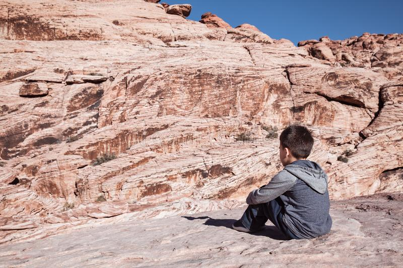 Little boy sitting on rocks and enjoying view of mountains on a sunny spring day stock images