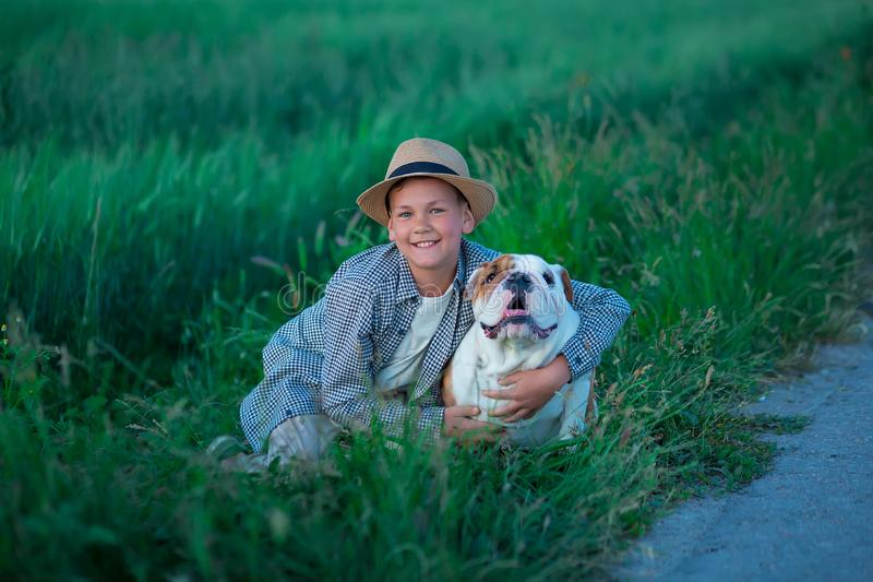 Little boy sitting standing with his english bull dog on the meadow of green rye. Handsom kid posing with best friend wearing. Stylish clothes and rustic retro royalty free stock photos