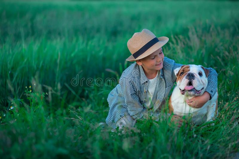 Little boy sitting standing with his english bull dog on the meadow of green rye. Handsom kid posing with best friend wearing. Stylish clothes and rustic retro stock image
