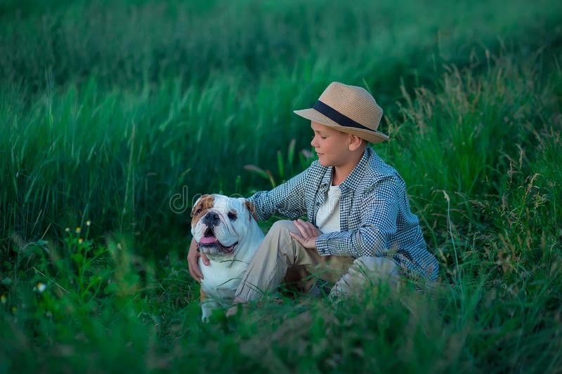 Little boy sitting standing with his english bull dog on the meadow of green rye. Handsom kid posing with best friend wearing. Stylish clothes and rustic retro royalty free stock images