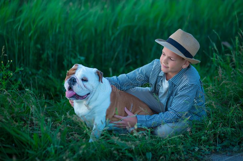 Little boy sitting standing with his english bull dog on the meadow of green rye. Handsom kid posing with best friend wearing. Stylish clothes and rustic retro royalty free stock photography
