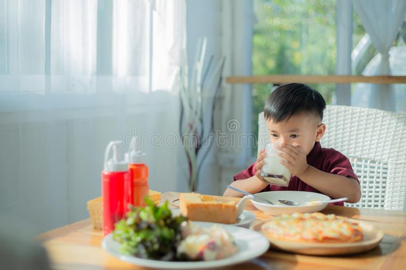 Little boy sitting at the table, eating breakfast royalty free stock photo