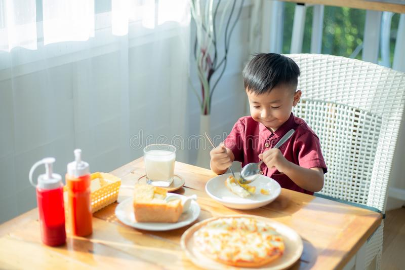 Little boy sitting at the table, eating breakfast stock photos