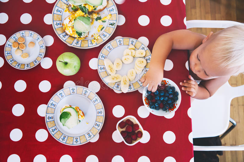 Little boy sitting at the table, eating breakfast. stock images