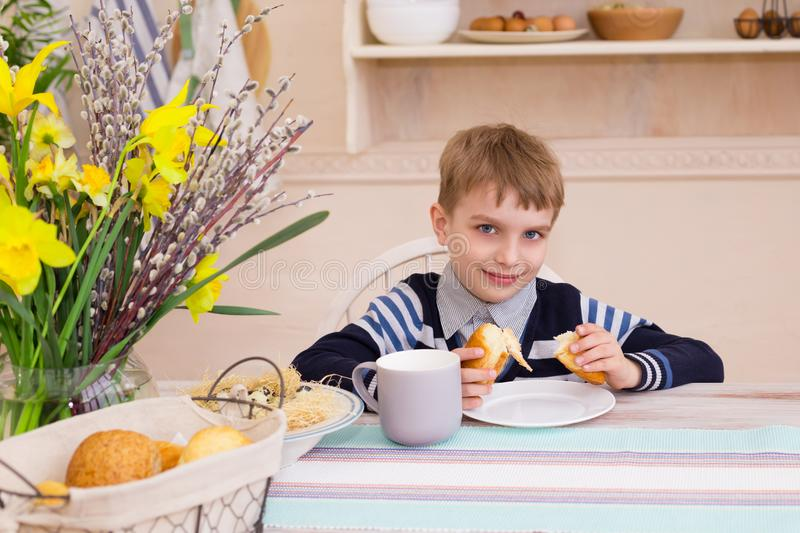 Little boy sitting at the table and eating breakfast in the kitchen. stock photos