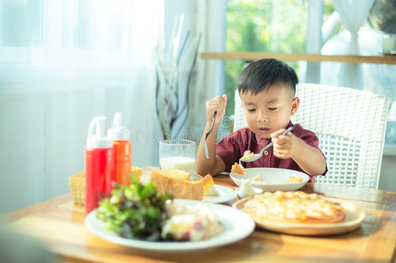 Little boy sitting at the table, eating breakfast royalty free stock photography