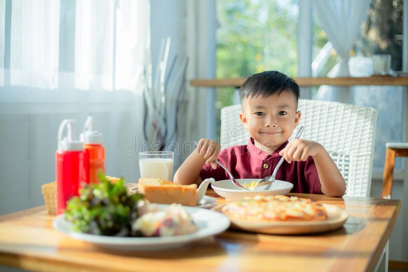 Little boy sitting at the table, eating breakfast stock photo