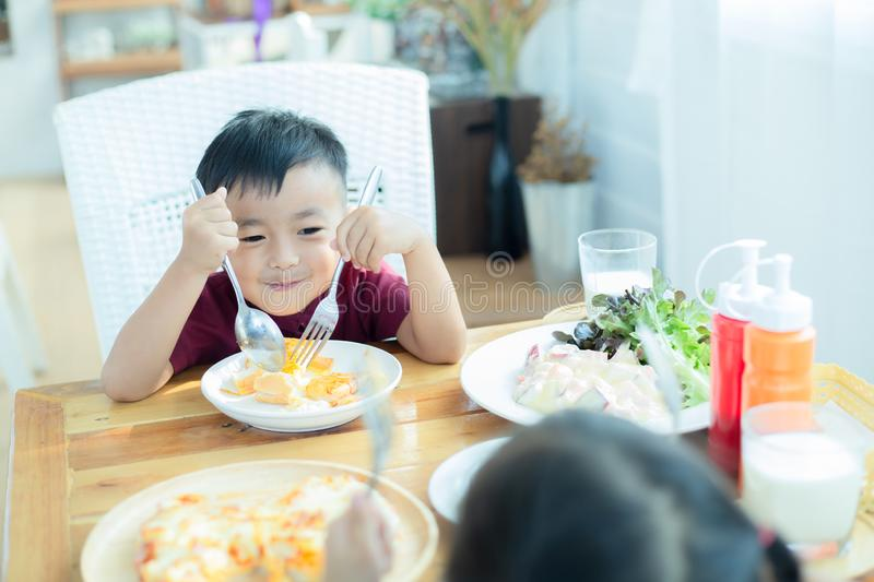 Little boy sitting at the table, eating breakfast royalty free stock images
