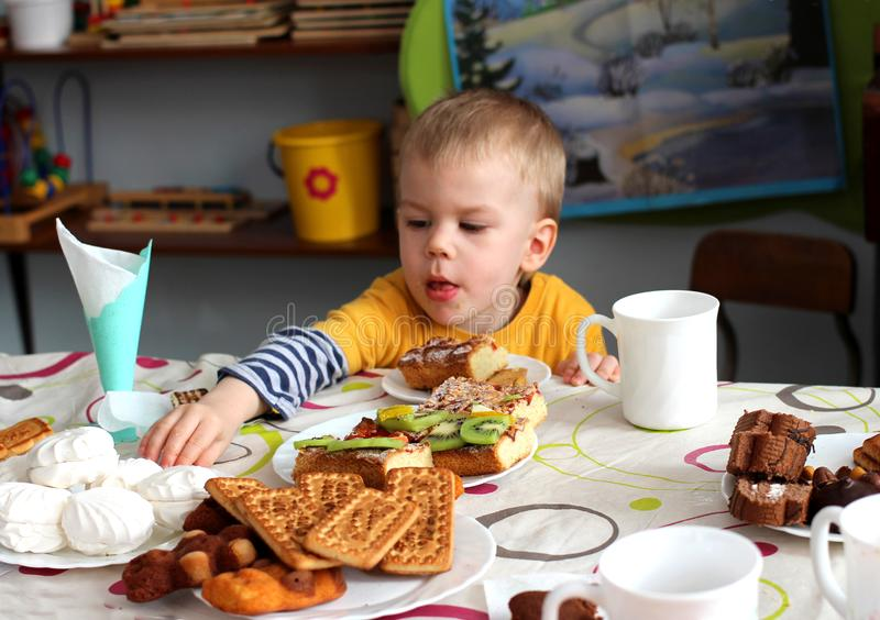 Little boy sitting at the table eating stretches to delicious candy stock photos