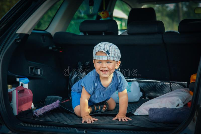 A small child sitting in the trunk of the car plays and laughs royalty free stock photos