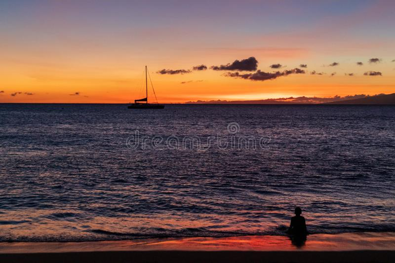 Little boy sitting in the warm Hawaiian ocean, watching the beautiful sunset royalty free stock images