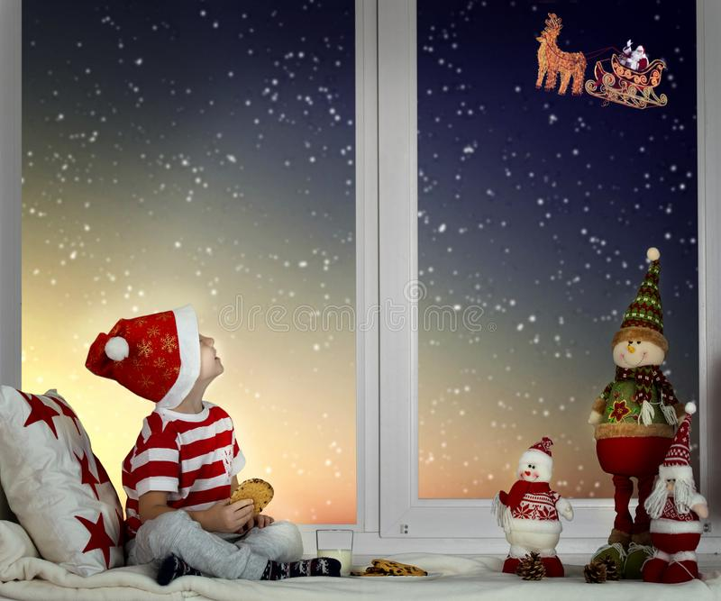 Happy holidays! Little boy sitting on the window and looking at Santa Claus flying in his sleigh against moon sky. Little boy sitting on the window and looking royalty free stock image
