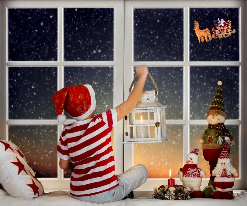 Little boy sitting on the window and looking at Santa Claus flying in his sleigh against moon sky. Room decorated on Christmas stock photography