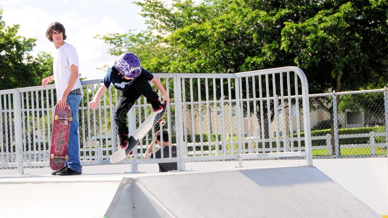 Little boy skateboarder hand up. Small kid jumps up a ramp in city park in South Florida stock photo