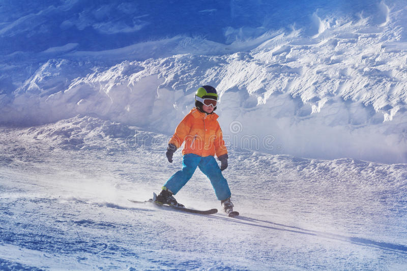 Little boy ski down the mountain by himself. Portrait of a little child ski down the track by his own in skiing school royalty free stock photography