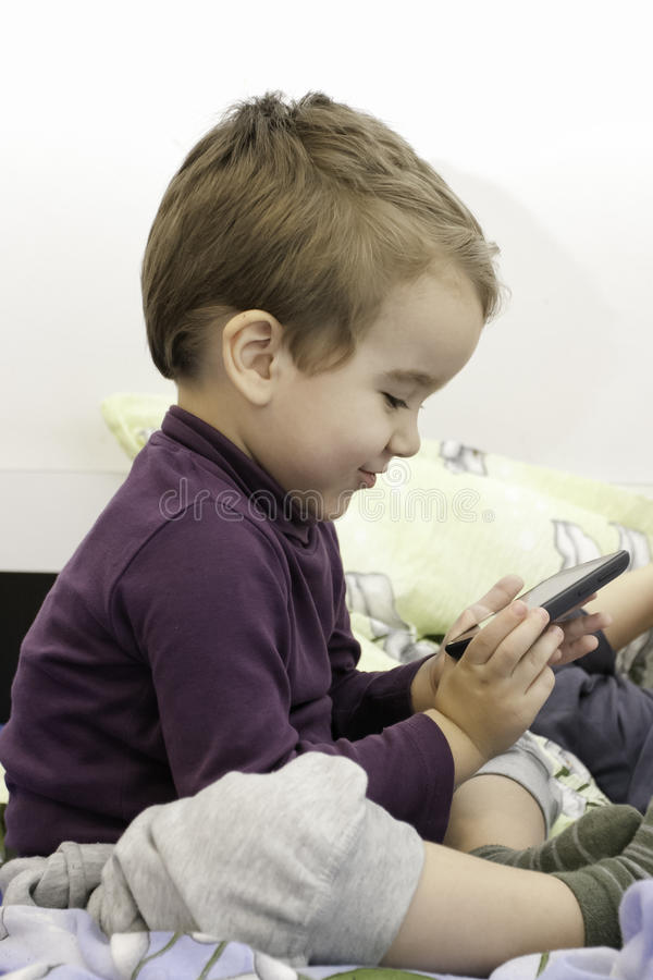 Little boy with smartphone at home playing stock photography