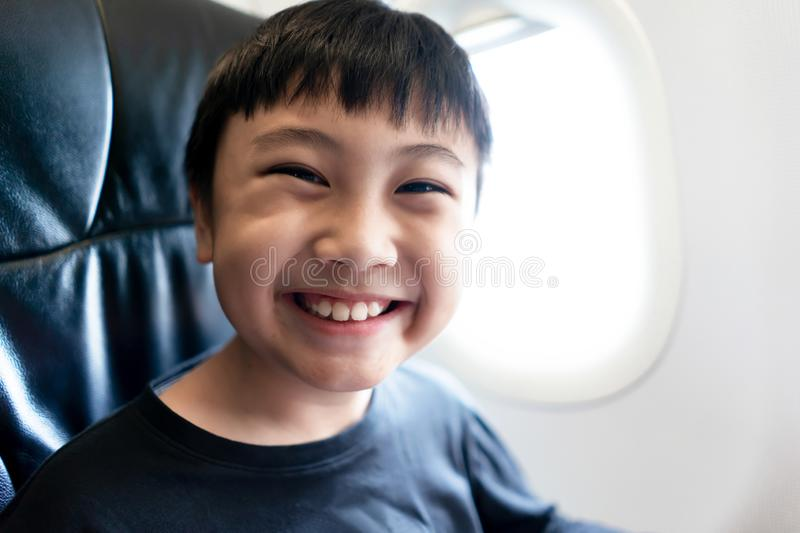 Little boy smile in air plane for travel on summer holiday stock photos