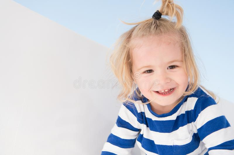 Little boy smile in navy clothes. Happy child enjoy sunny day. Kid smiling with blond hair ponytail. Kids fashion and style. Summe royalty free stock photos