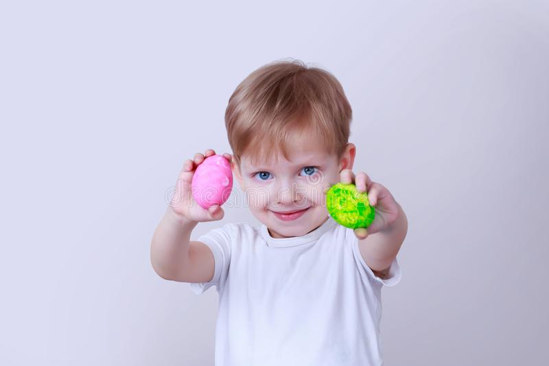 Boy with painted eggs. Little boy smiles and holds in his hands a two painted eggs royalty free stock image