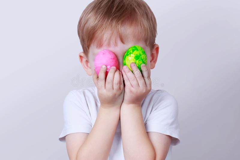 Boy with painted eggs. Little boy smiles and holds in his hands a two painted eggs royalty free stock photos