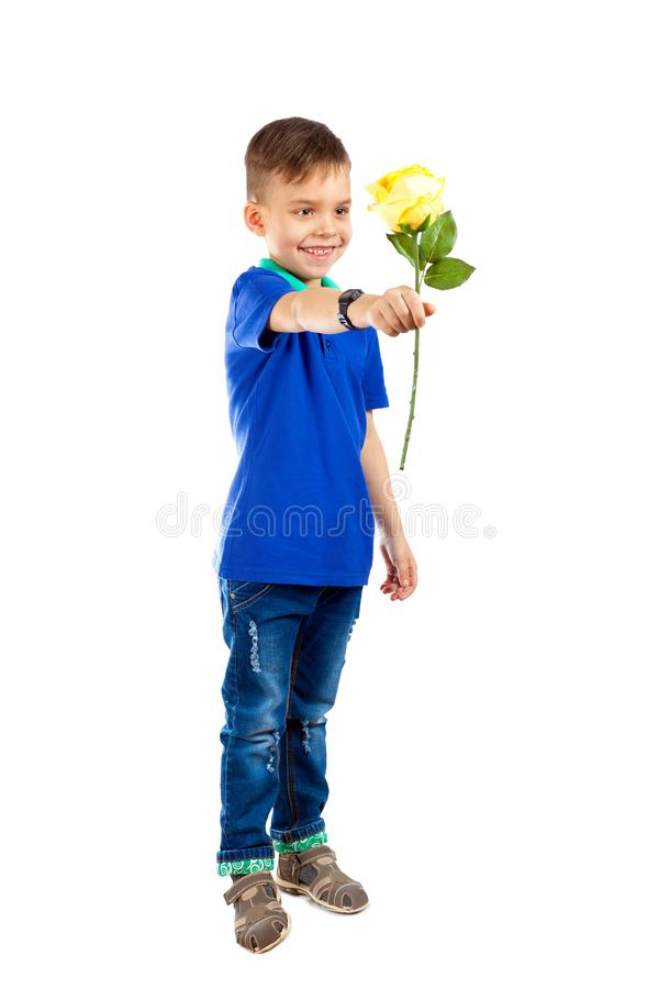 The little boy smiles and holds out a flower royalty free stock image