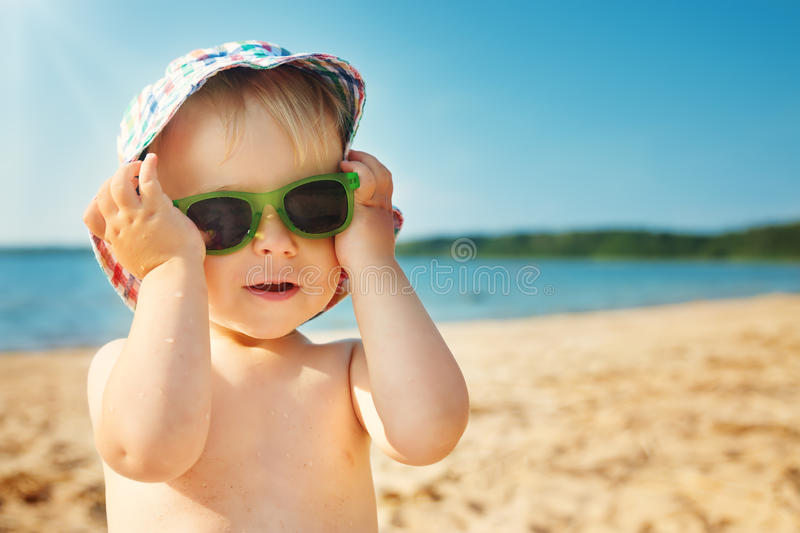 Little boy smiling at the beach in hat with sunglasses. One year old boy smiling at the beach in hat with sunglasses. Child on vacations at sea royalty free stock photography