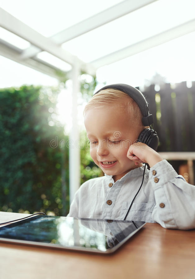 Little boy smiling in delight listening to music. Little boy smiling in delight, as he listens to music downloaded on his tablet-pc using stereo headphones while royalty free stock image