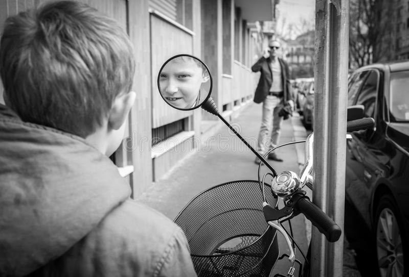 Little boy smiling at the scooter rear view mirror royalty free stock photography
