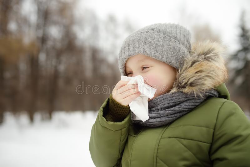 Little boy sneezing and wipes nose with napkin during walking in winter park. Flu season and cold rhinitis. Allergic kid stock images