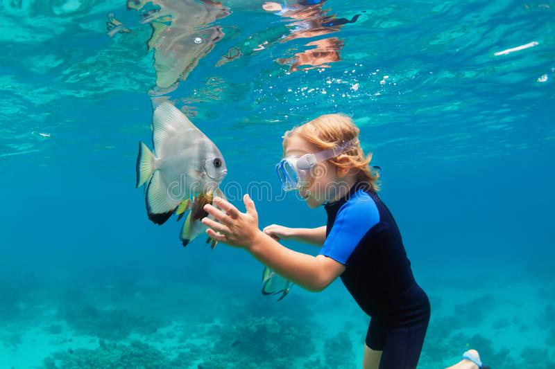 Little boy in snorkeling mask dive underwater with tropical fishes. Happy family - active kid in snorkeling mask dive underwater, see tropical fish Platax royalty free stock photography