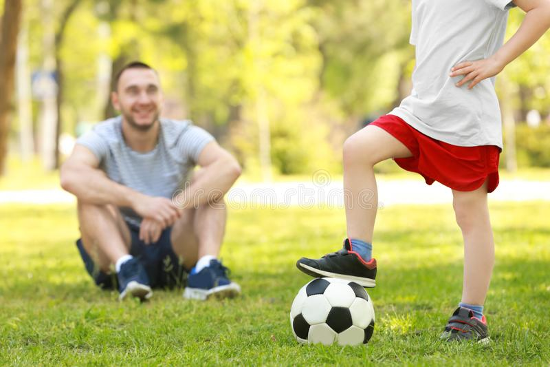 Little boy with soccer ball in green park and his blurred father. On background royalty free stock image