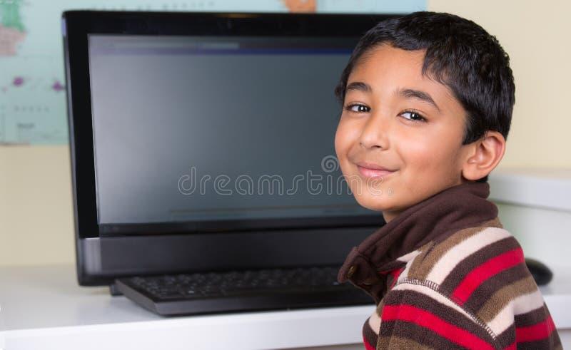 Little Boy som arbetar på en dator royaltyfri foto