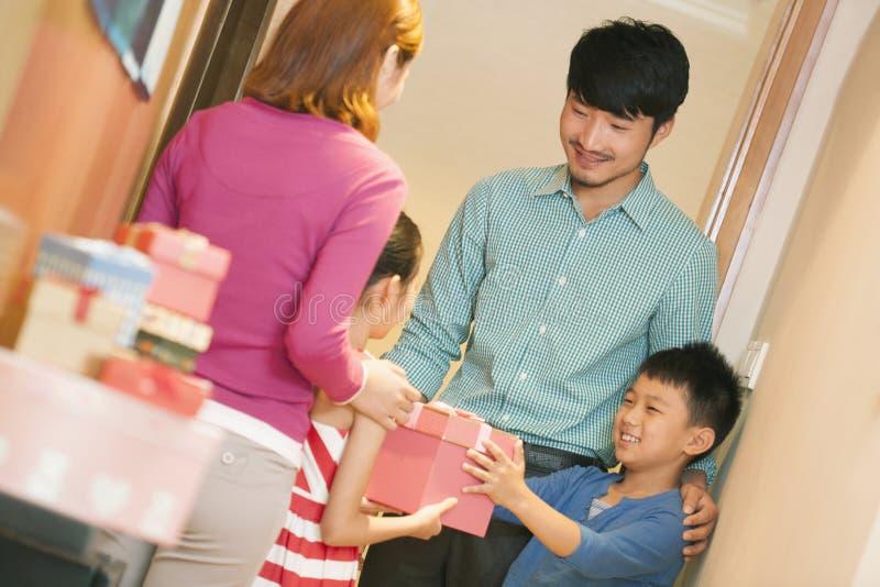 Little Boy som ger liten flicka en gåva arkivfoto