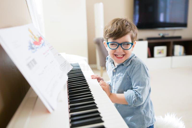 Little Boy som spelar pianot fotografering för bildbyråer