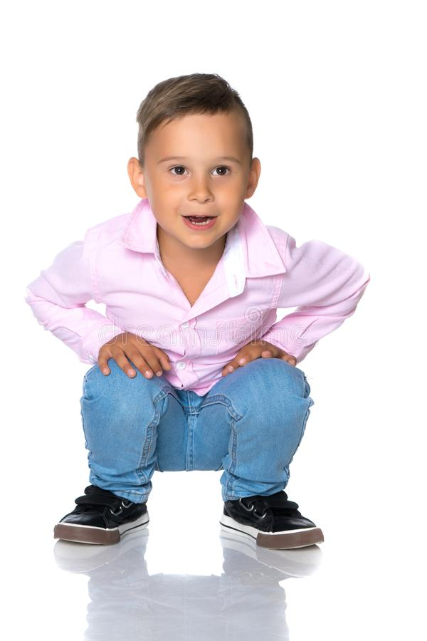 The little boy squatted down. stock images
