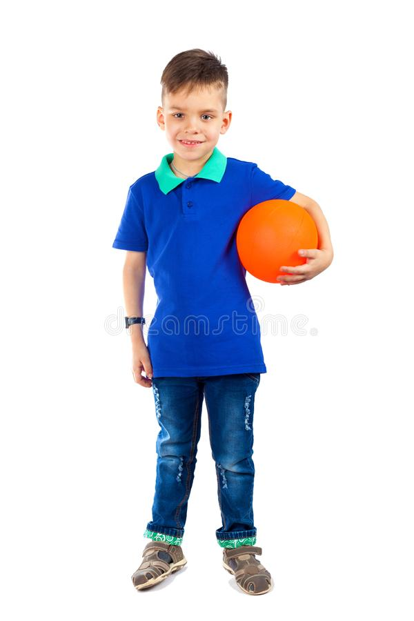 A little boy is standing with the ball under his arm stock photos