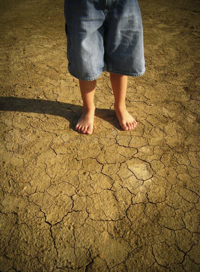 Little boy standing in desert stock images